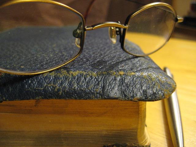 Ecke eines alten Buches, Brille und Kuli (Ausschnitt)